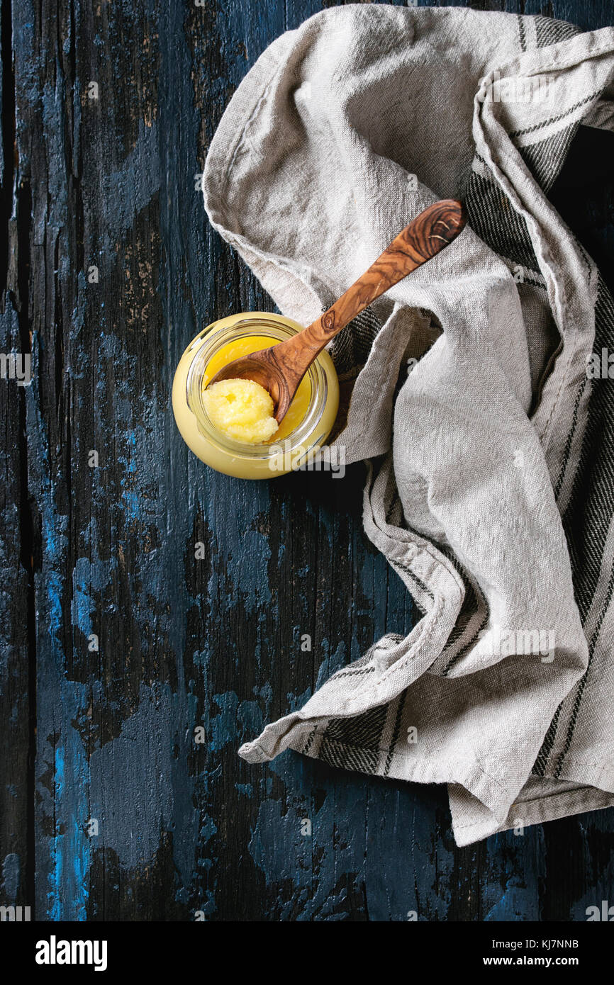 Glass of drawn ghee butter standing with wood spoon and linen textile over old dark blue wooden background. Healthy - Stock Image
