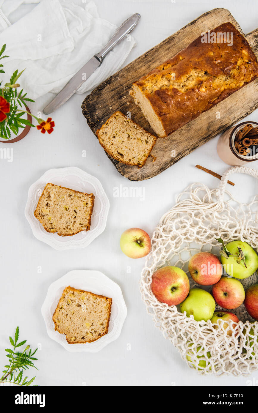 Cinnamon apple bread sliced on a wooden cutting board photographed from top view. Apples in a net bag and apple - Stock Image