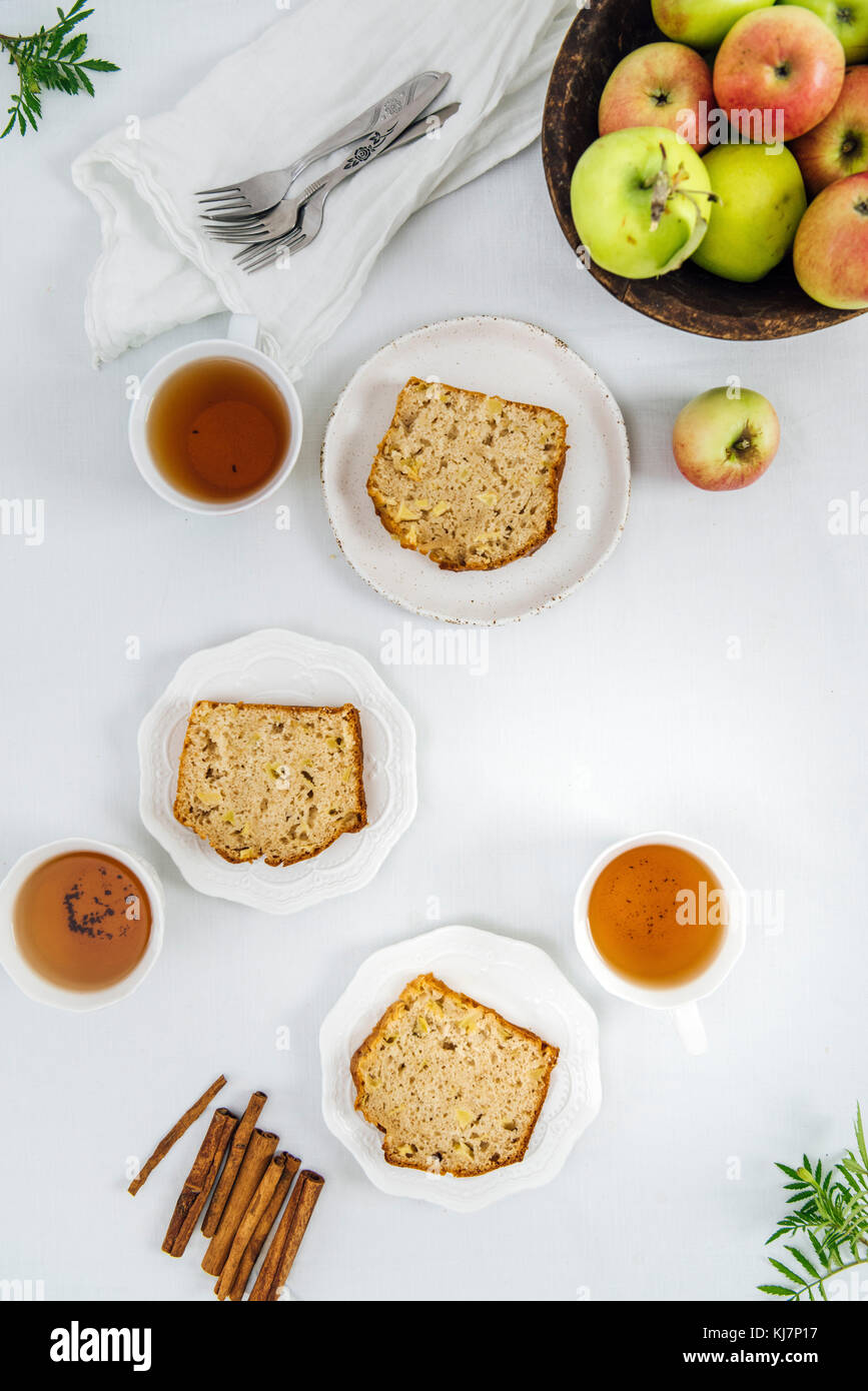Cinnamon apple bread slices served on three white plates photographed from top view. Three cups of tea and apples - Stock Image