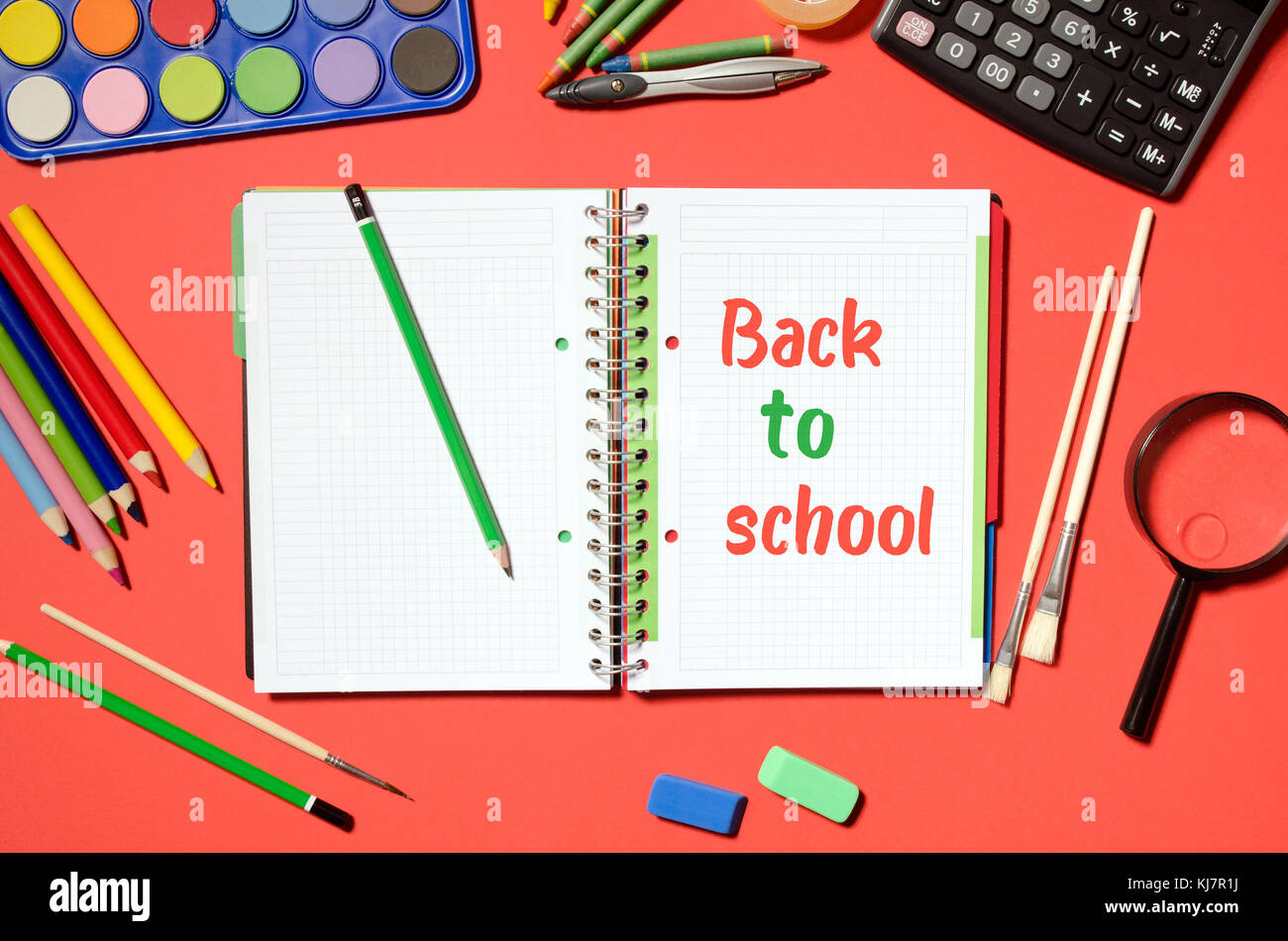 Notepad with back to school words and office stationery, red background.  stationery office desk top view table - Stock Image