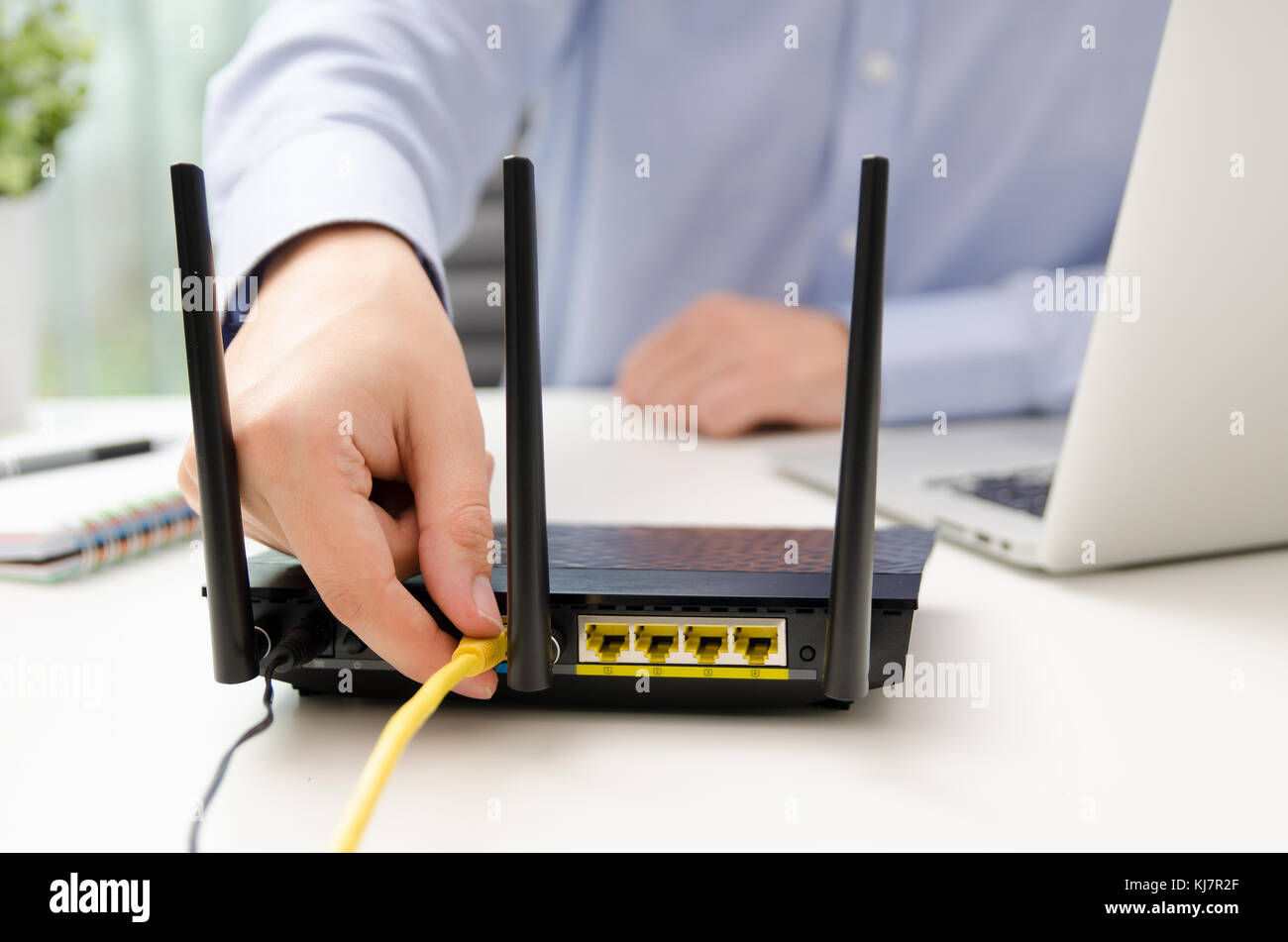 Sensational Man Plugs Ethernet Cable Into Router Router Wireless Wire Broadband Wiring 101 Tzicihahutechinfo