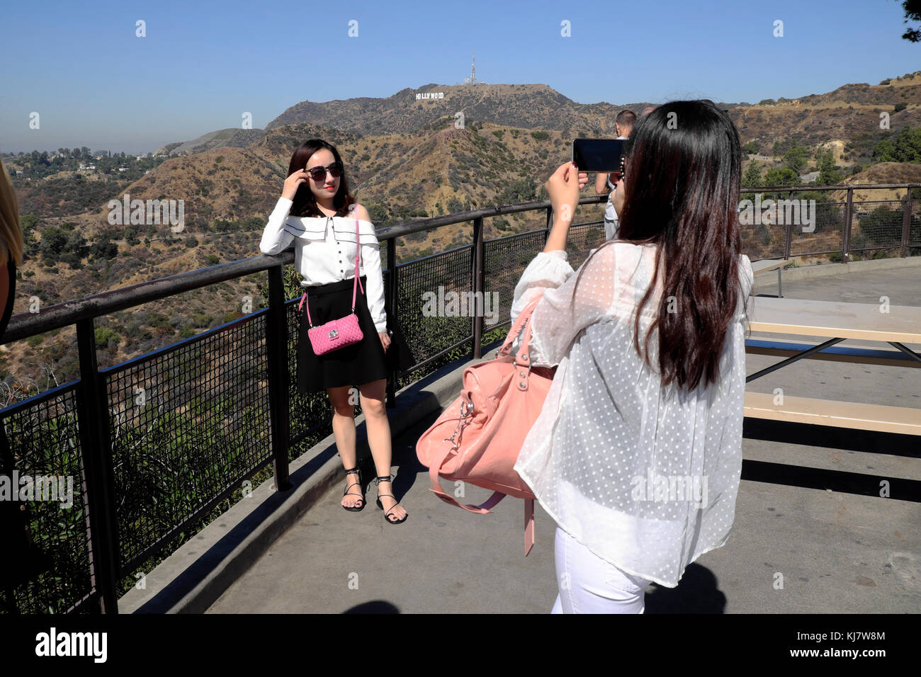 Young Chinese woman taking photo of friend with iphone camera & Hollywood sign at Griffith Park Observatory Los Angeles, California  USA KATHY DEWITT Stock Photo