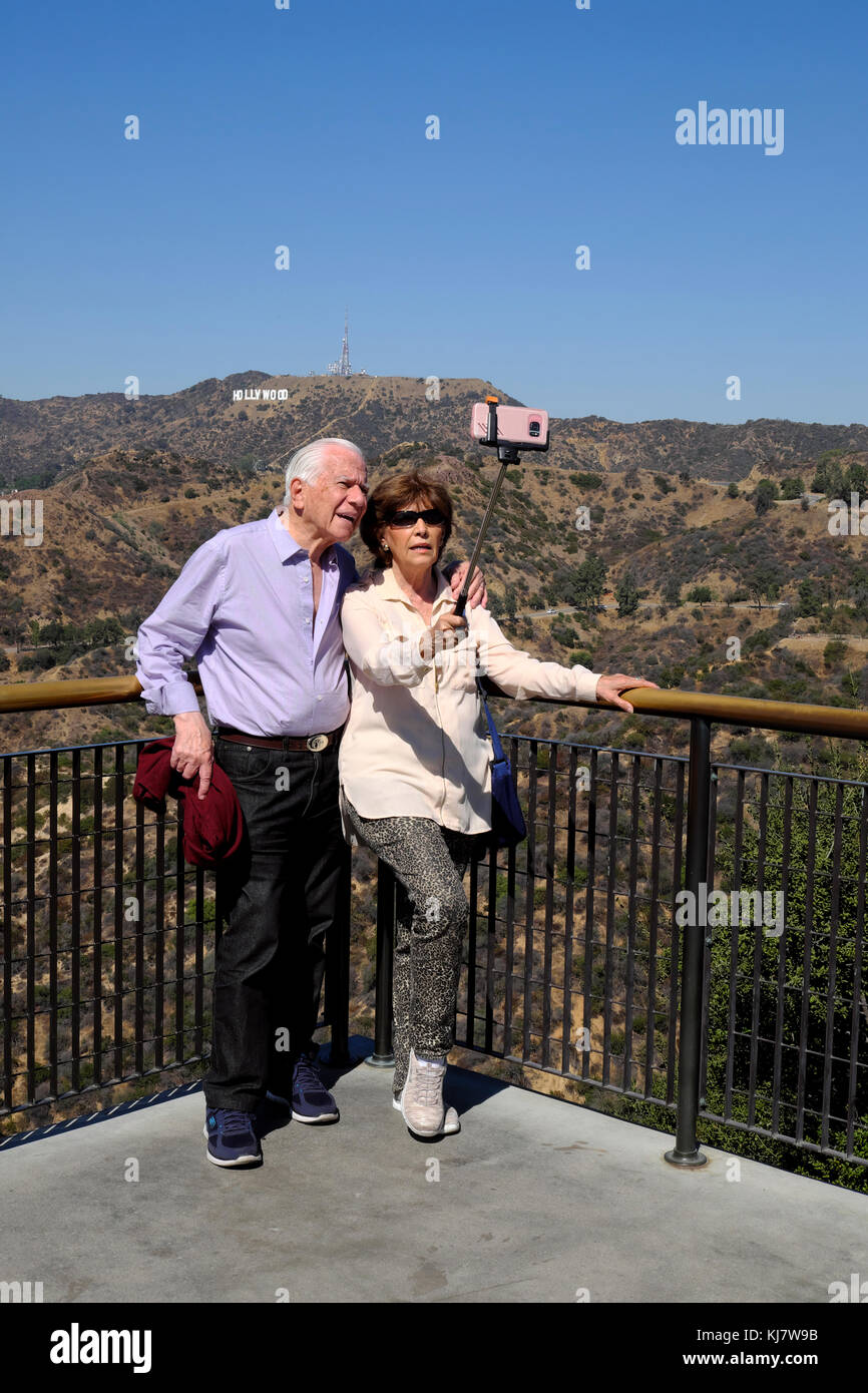 Senior couple holding selfie stick taking cell phone photo in front of Hollywood sign Griffith Park Observatory - Stock Image