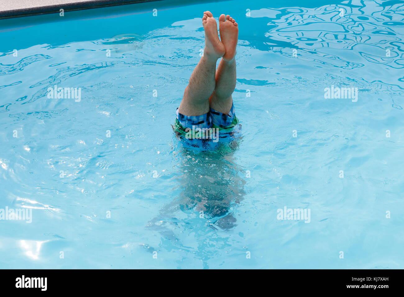 Handstand im Wasser, Beine strecken in die Luft - Stock Image