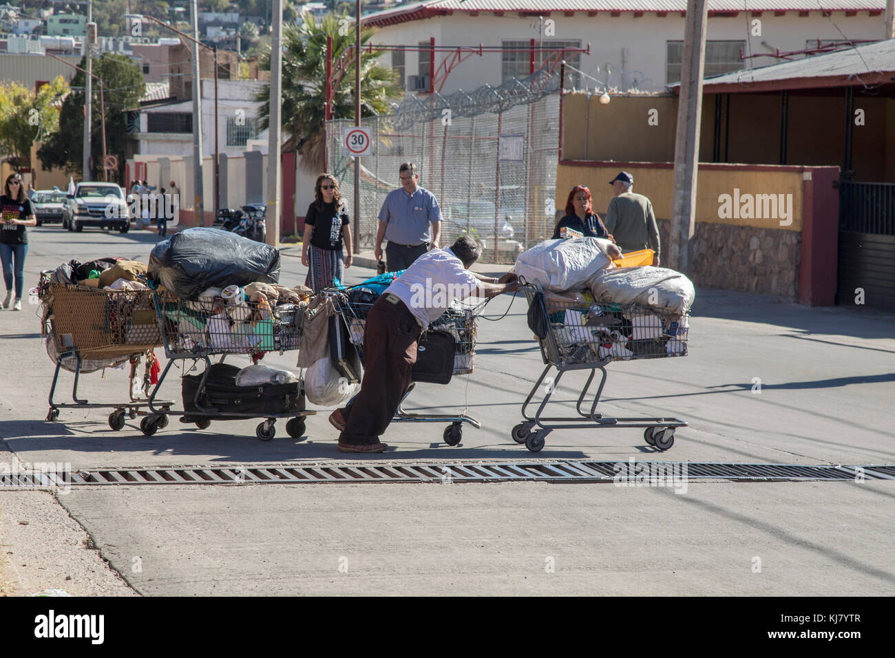 Nogales, Sonora Mexico - A man pushes four supermarket carts of belongings on a Nogales street. - Stock Image