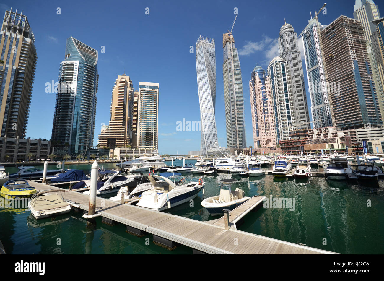 Boats on marina in Dubai with tall city skyscrapers in background - Stock Image