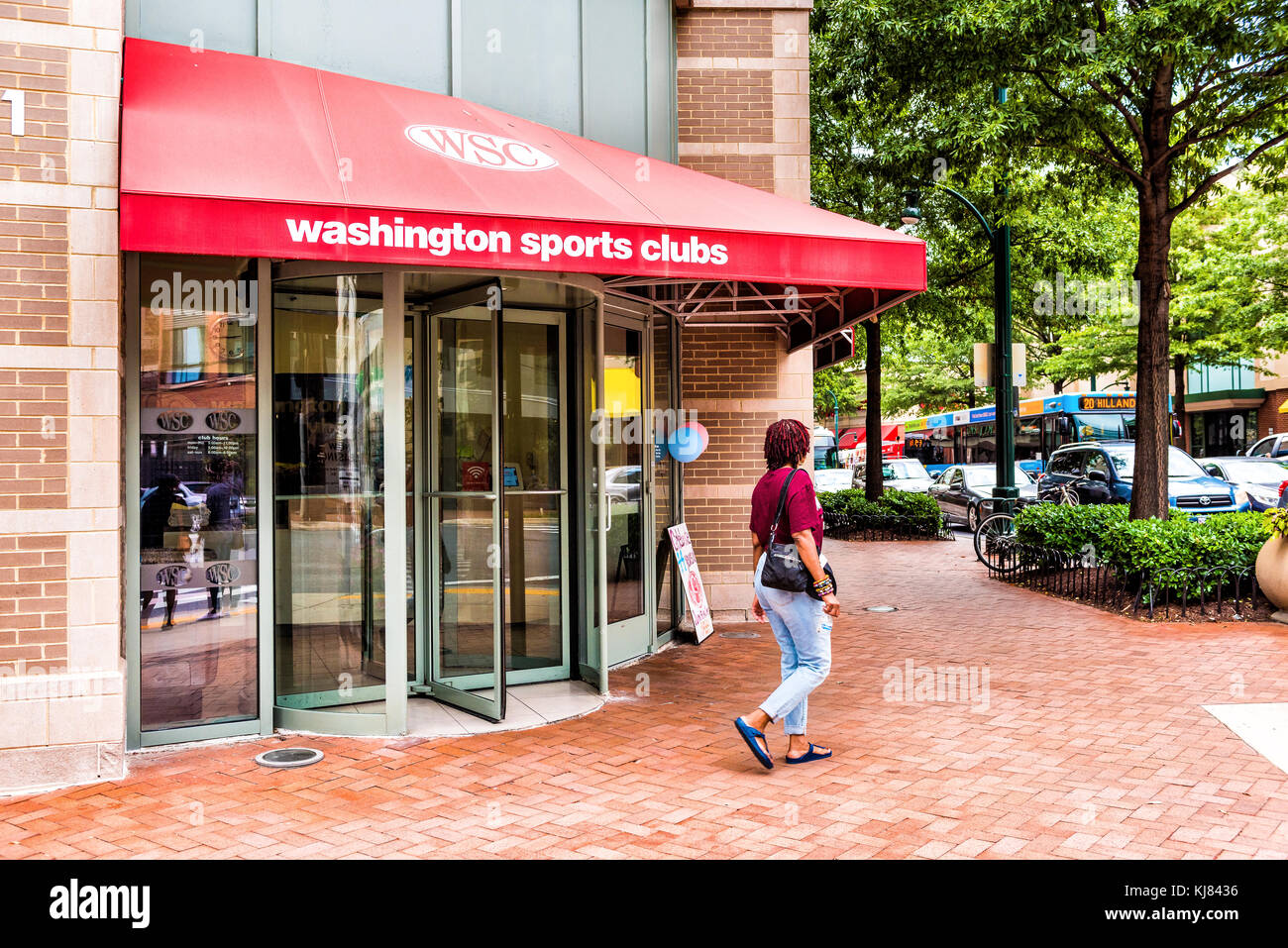 Silver Spring, USA - September 16, 2017: Woman walking by Washington Sports Clubs gym entrance in downtown area Stock Photo