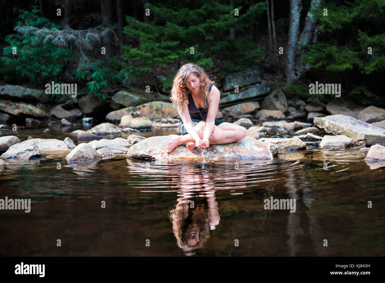 Young woman enjoying nature on peaceful, calm Red Creek river in Dolly Sods, West Virginia during sunny day with - Stock Image