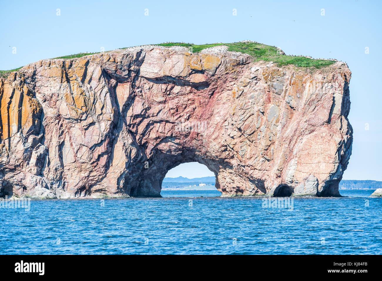 Rocher Perce rock in Gaspe Peninsula, Quebec, Gaspesie region closeup with blue water - Stock Image