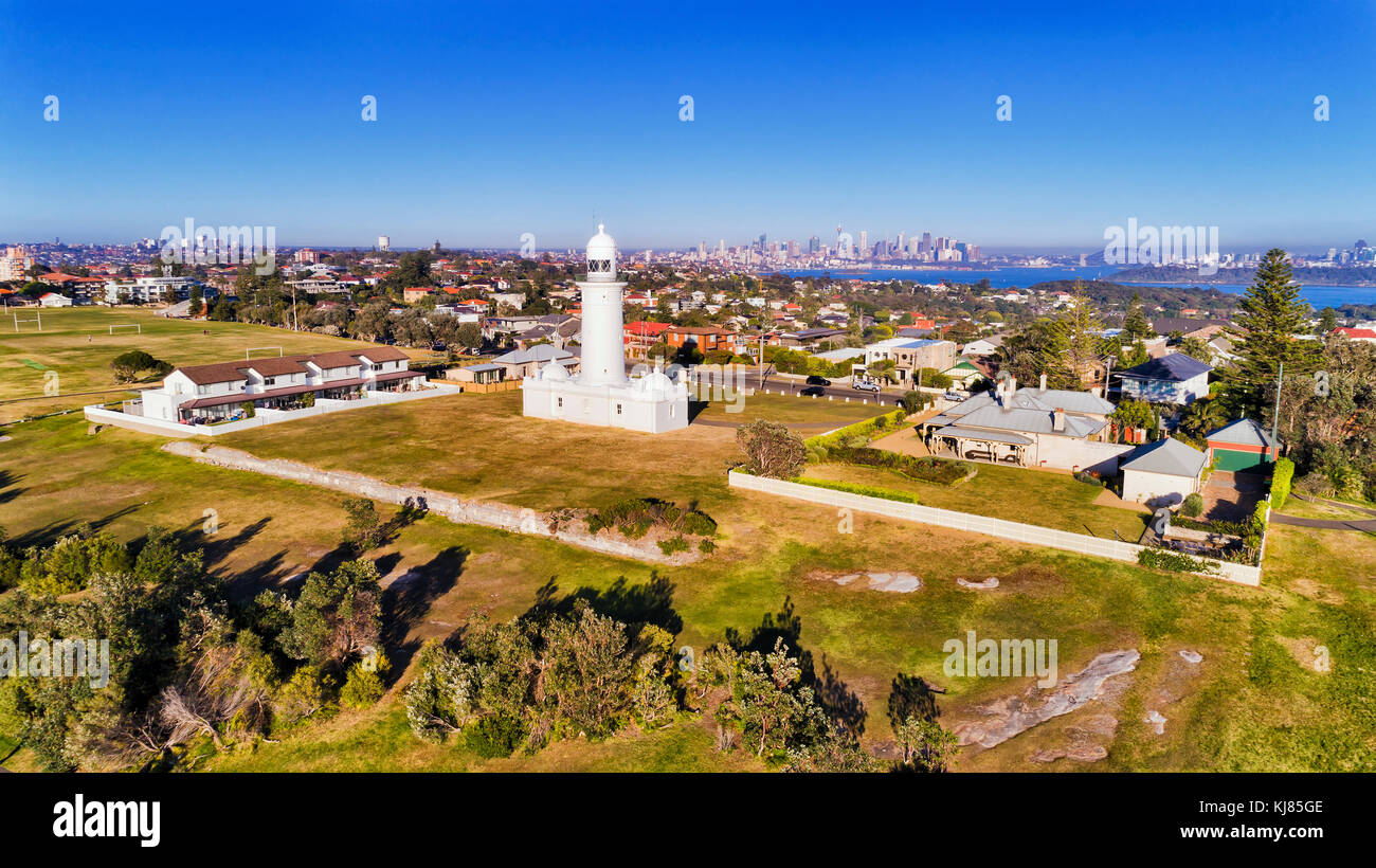 White historic Macquarie lighthouse on elevated South Head headland overlooking Watsons bay eastern suburb in Sydney - Stock Image