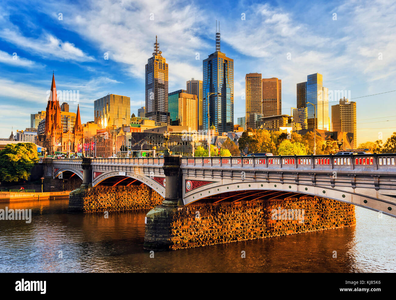 Warm morning light on high-rise towers in Melbourne CBD above Princes bridge across Yarra river. Stock Photo