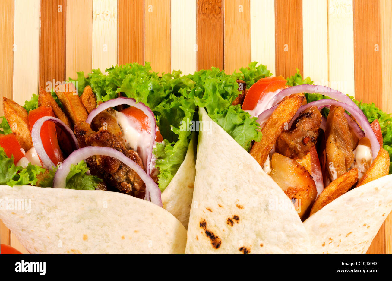 Pair of gyros pita on the wooden background - Stock Image