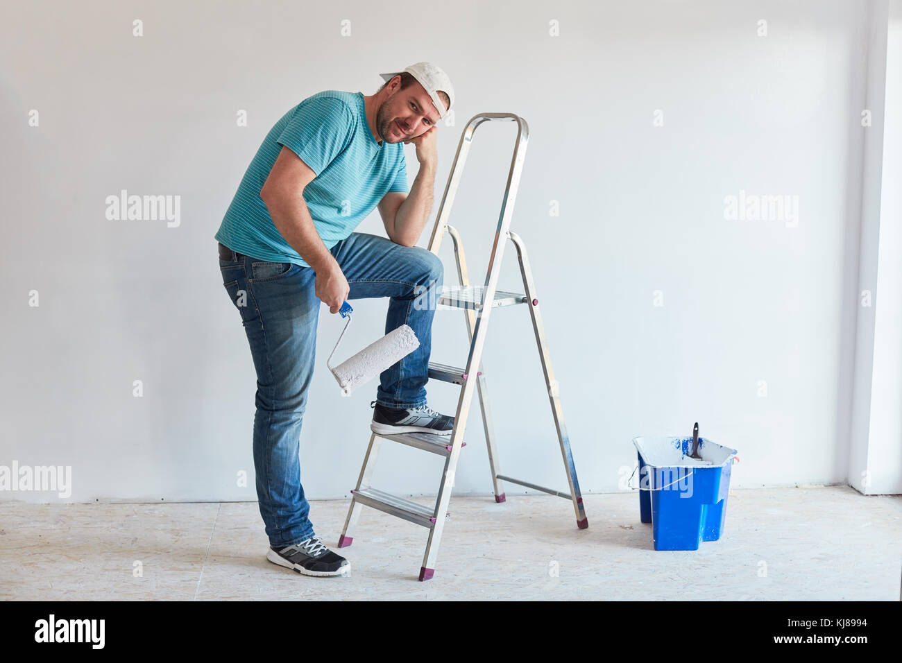The tired painter rests after painting - Stock Image