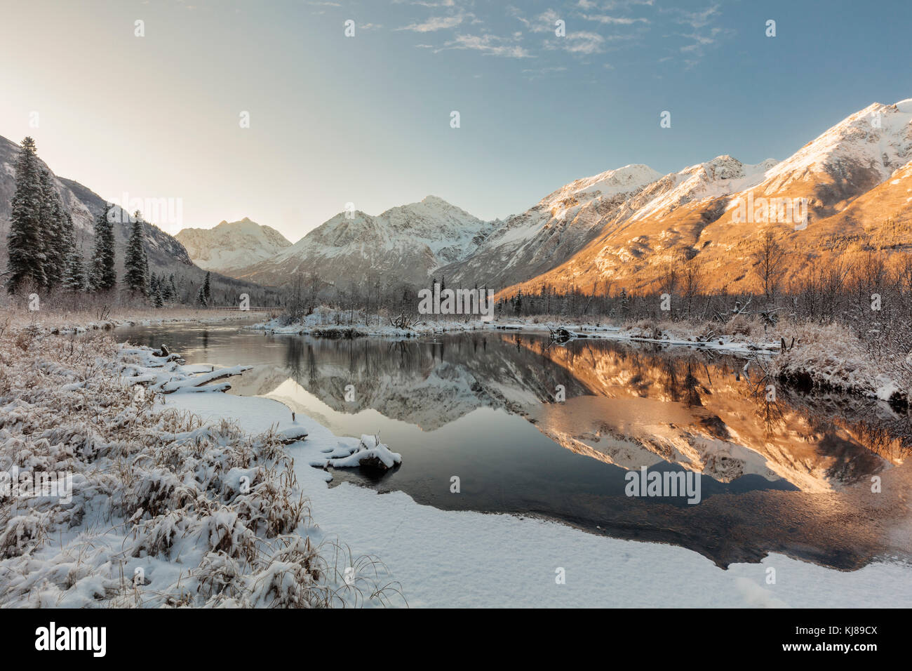 Dawn light illuminates the season's first snow as it blankets Eagle River Valley and the Chugach Mountains in - Stock Image