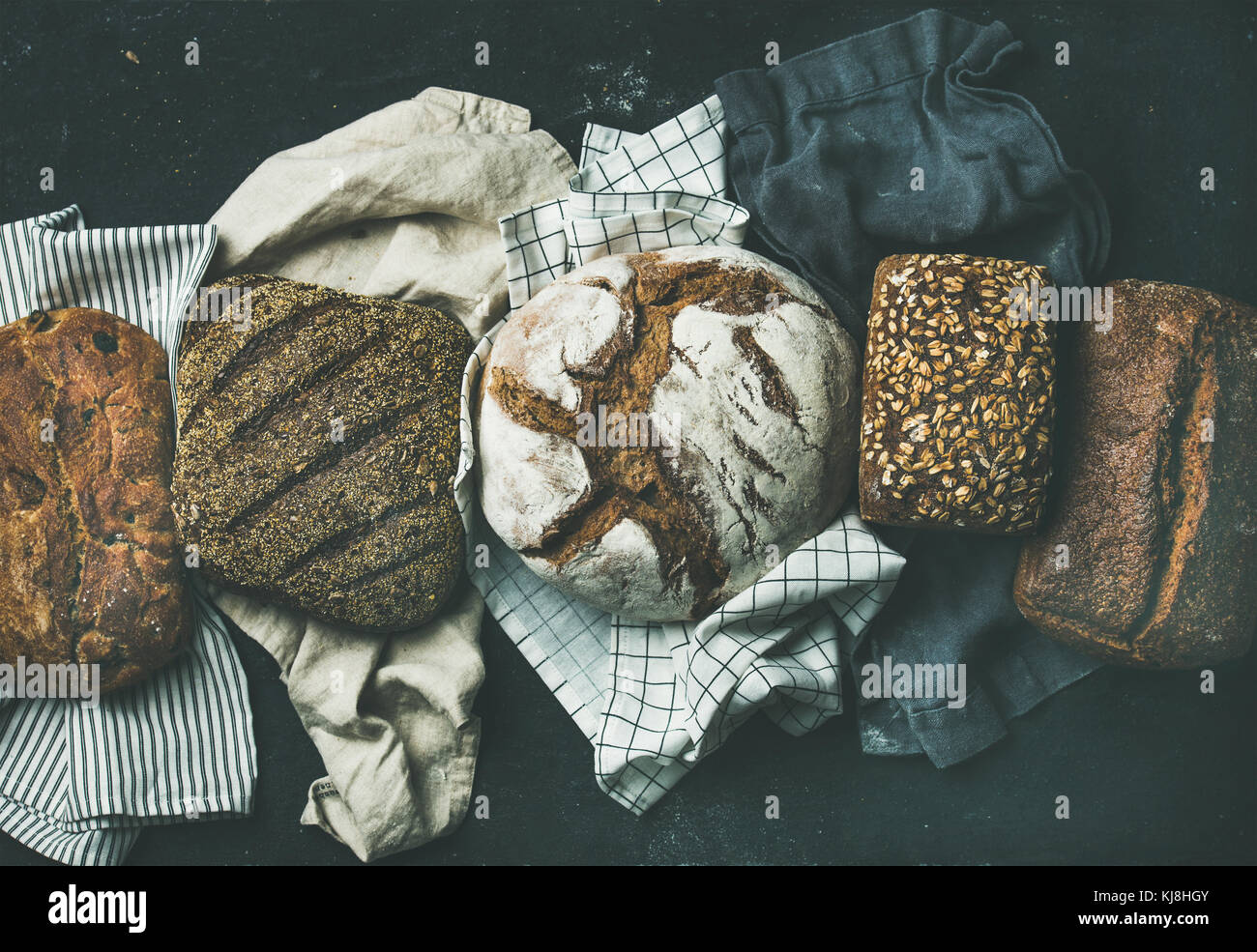 Various bread selection flat-lay, black background - Stock Image
