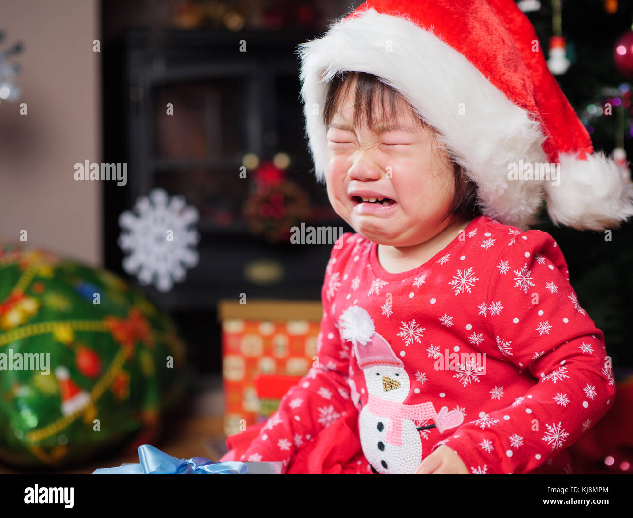crying baby girl missing her christmas gift Stock Photo