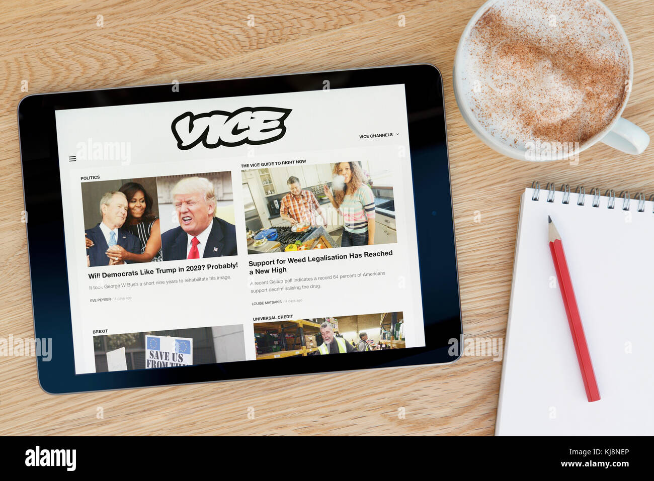The Vice website features on an iPad tablet device which rests on a wooden table beside a notepad and pencil and - Stock Image