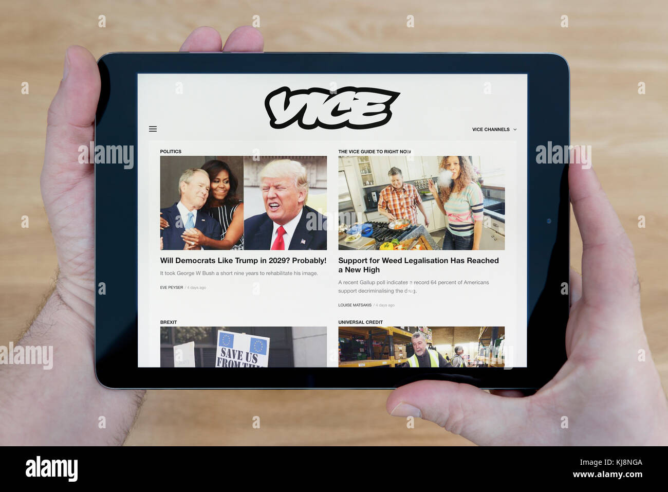 A man looks at the Vice website on his iPad tablet device, shot against a wooden table top background (Editorial - Stock Image