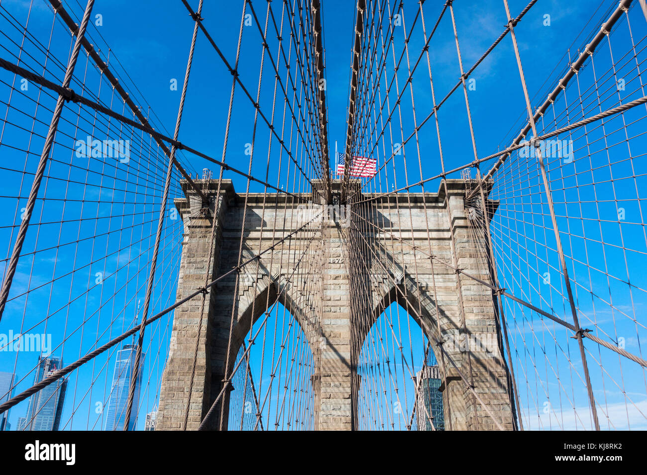 One of the stone towers of the Brooklyn Bridge and an American flag on top Stock Photo