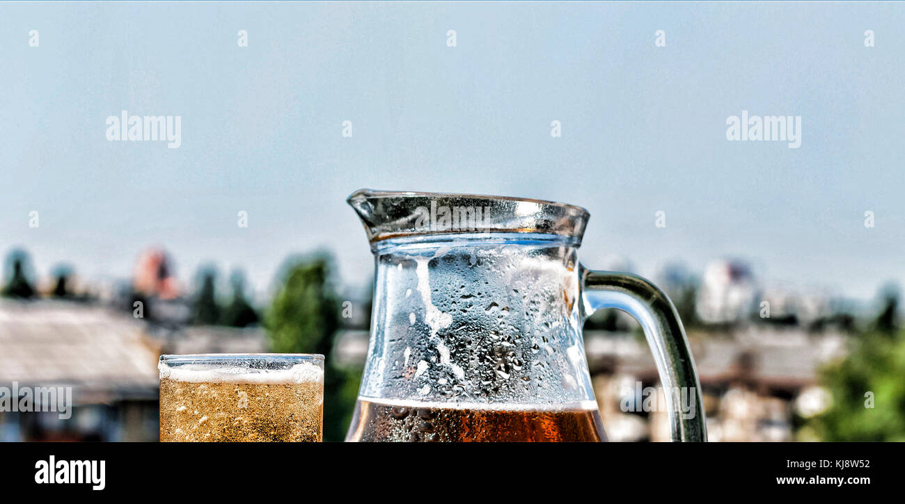 Crafting a beer in a jug and a glass. Summer time. close up - Stock Image