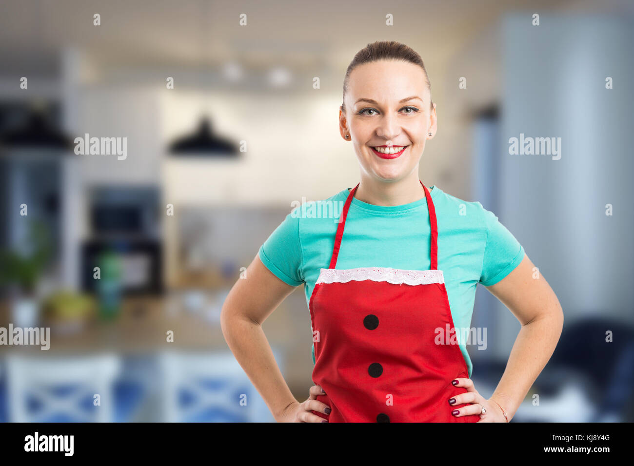 Wife or housekeeper smiling and wearing red apron on home kitchen background Stock Photo