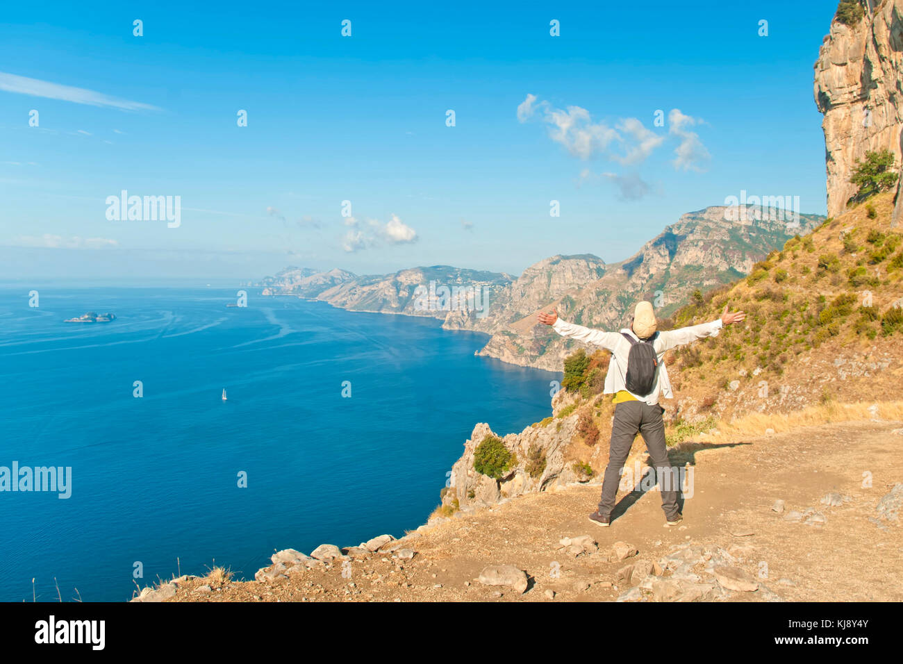 young male tourist in white shirt and cap standing at cliff edge with his arms open looking at sea and mountains - Stock Image