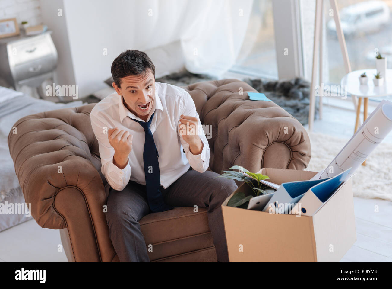 Emotional man clenching his fists while screaming loudly - Stock Image