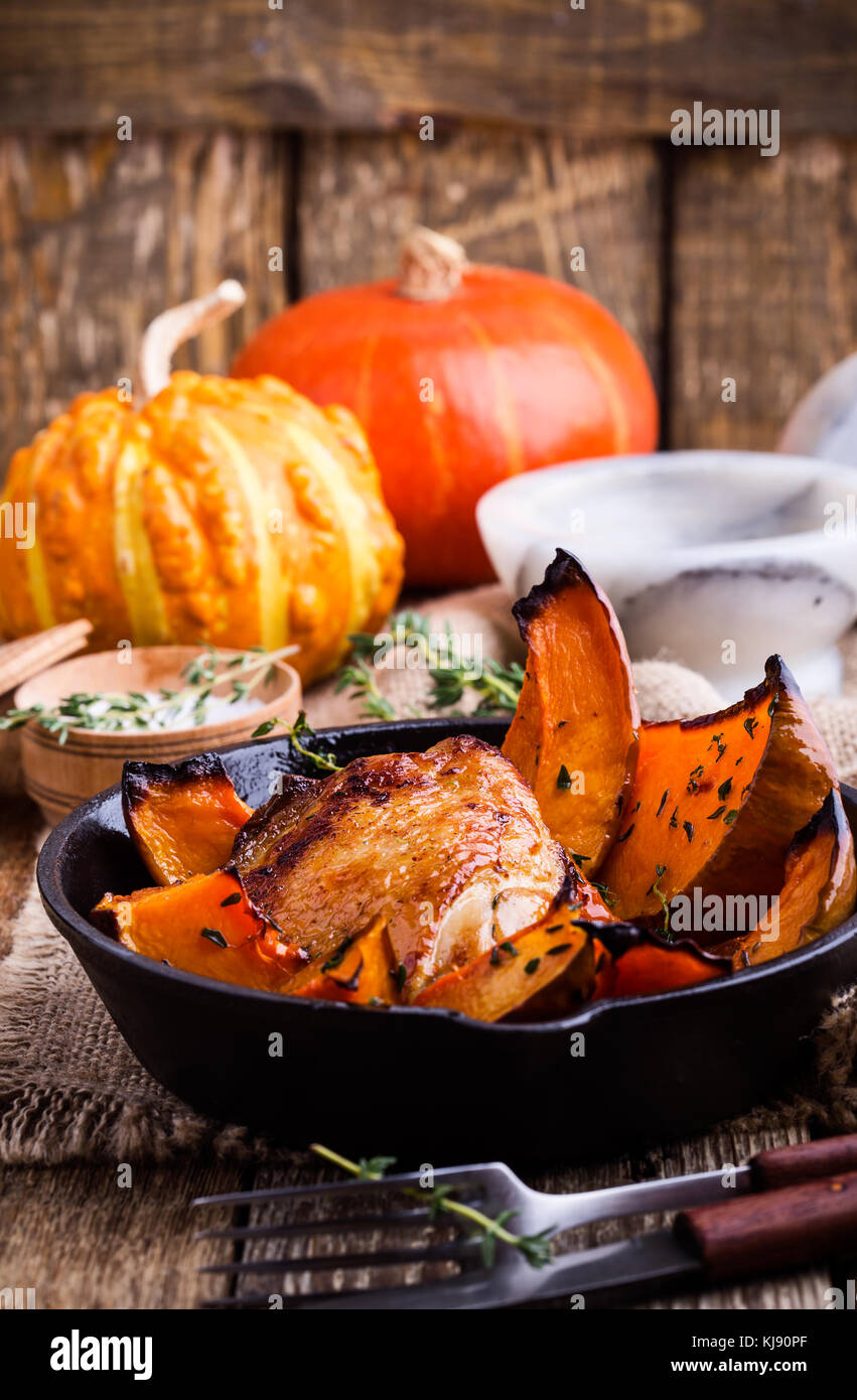 Homemade  Roast chicken thighs with butternut squash and thyme herb in cast iron skillet on rural wooden table Stock Photo