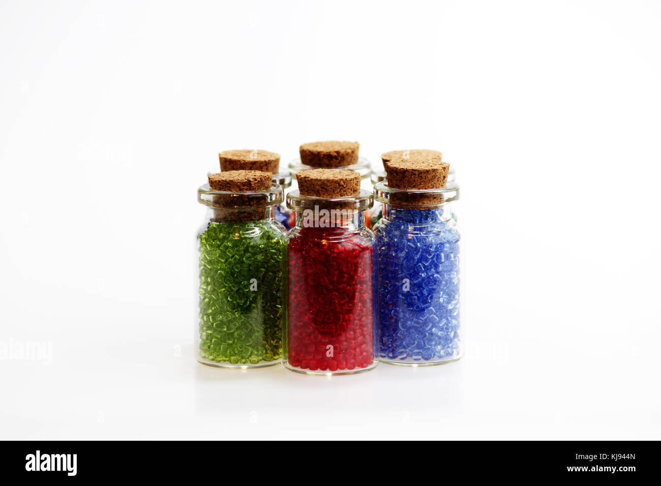 Six tiny glass bottles with a cork stopper, filled with a rainbow colours of beads, on a white background. Stock Photo