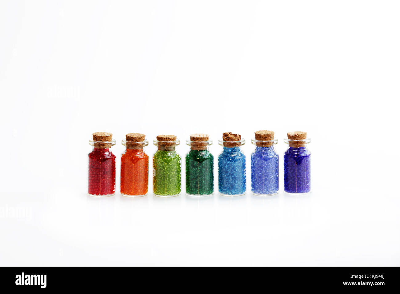 Seven tiny glass bottles with a cork stopper, filled with a rainbow colours of beads, on a white background Stock Photo