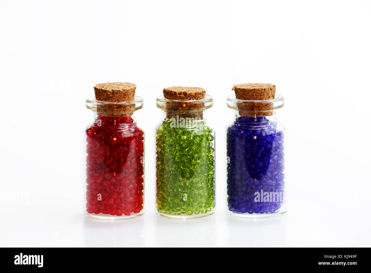 Three tiny glass bottles with a cork stopper, filled with a rainbow colours of beads, on a white background. Red, Stock Photo
