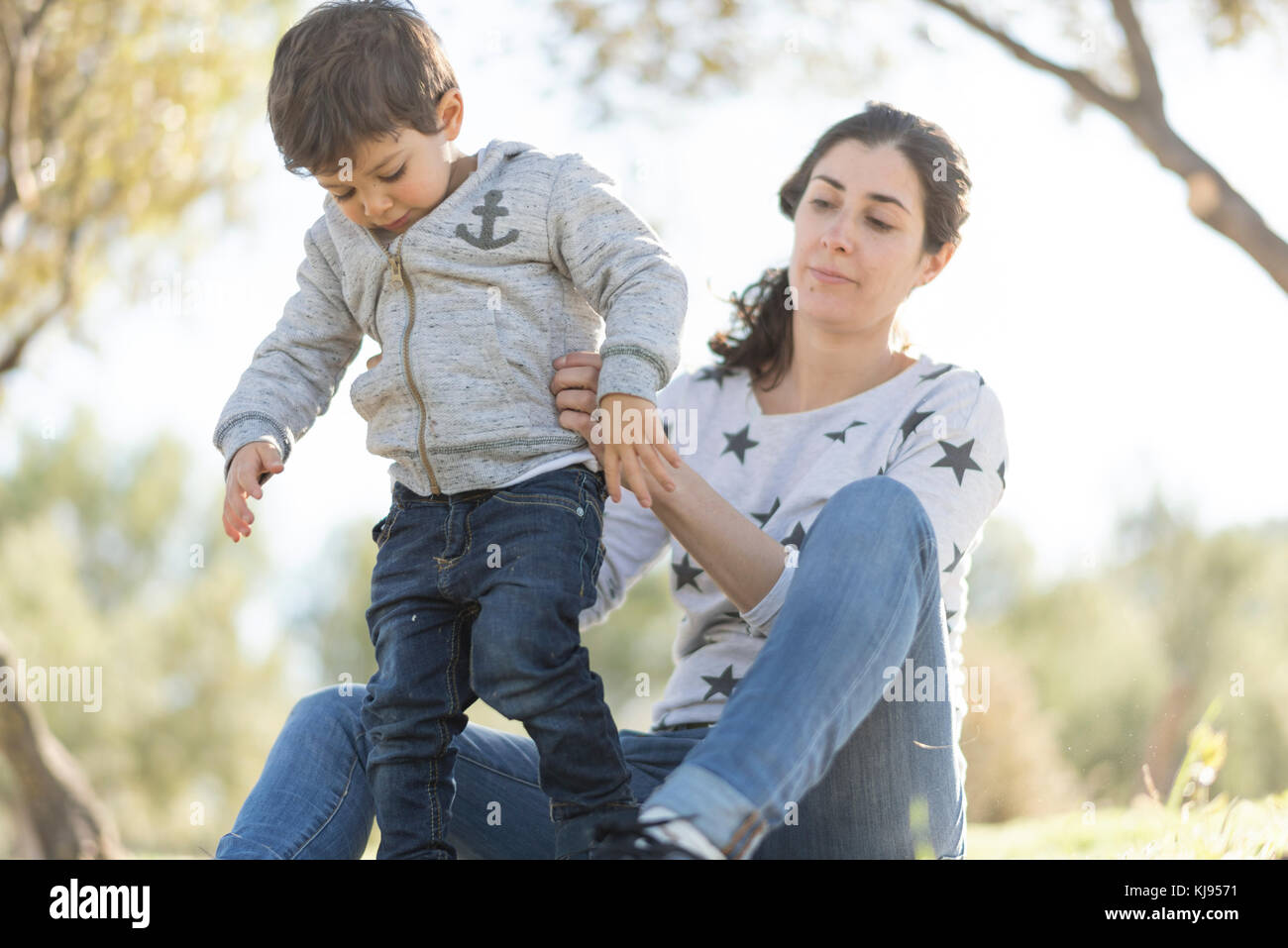 Mother and son in outdoors wood forest park. First steps learning - Stock Image