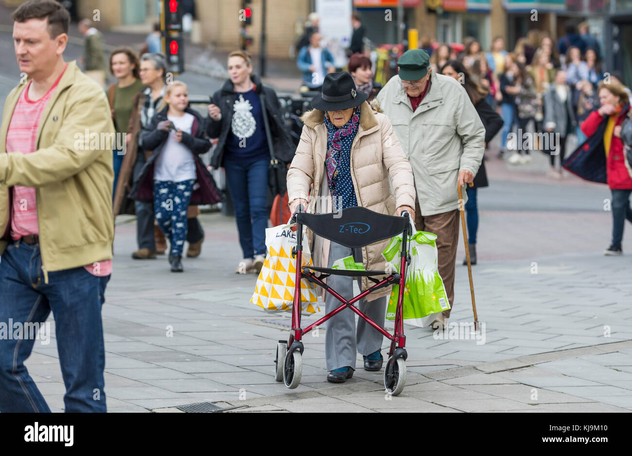 Elderly lady walking through a busy crowded city with the aid of a wheeled Zimmer frame in England, UK. Elderly - Stock Image
