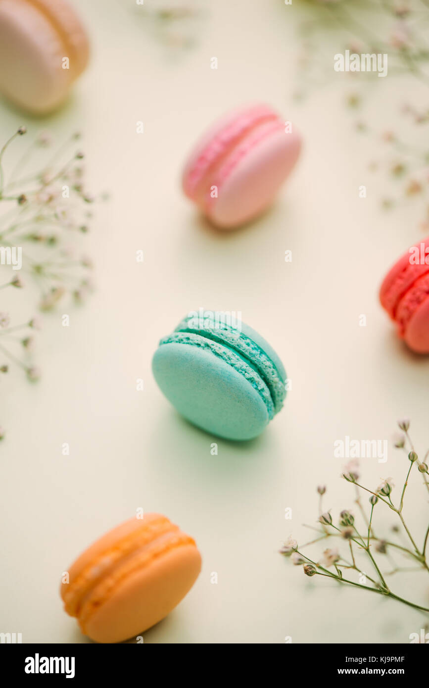 Morning cake macaron and flower gypsophila on light green background from above. Cozy breakfast. Flat lay style. - Stock Image