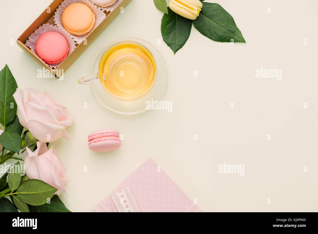 Colorful macaroons and rose flowers with tea on light green. Sweet macarons in gift box. Top view - Stock Image