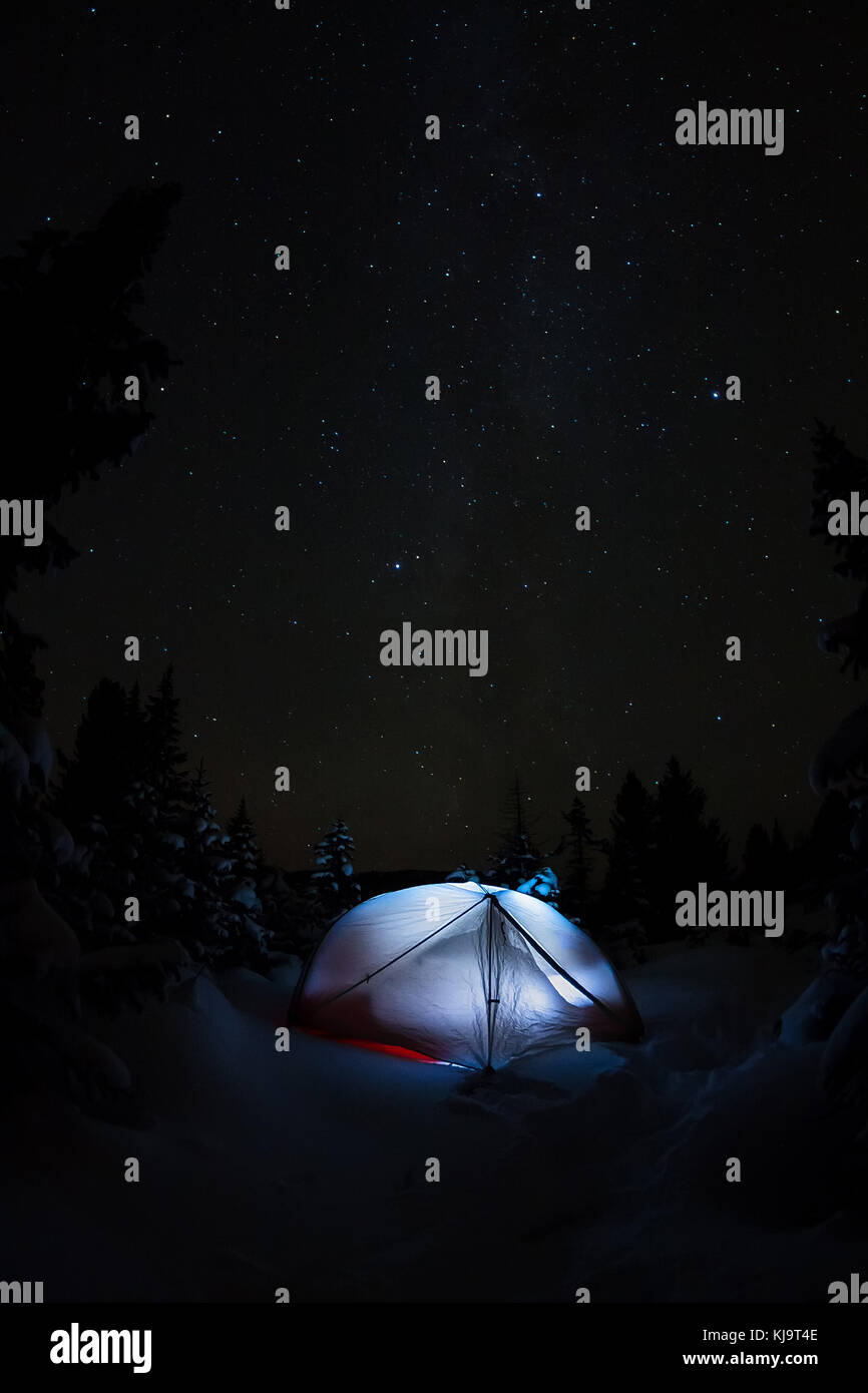 White tent under the starry sky and the milky way in the trees in the winter mountains at night. - Stock Image