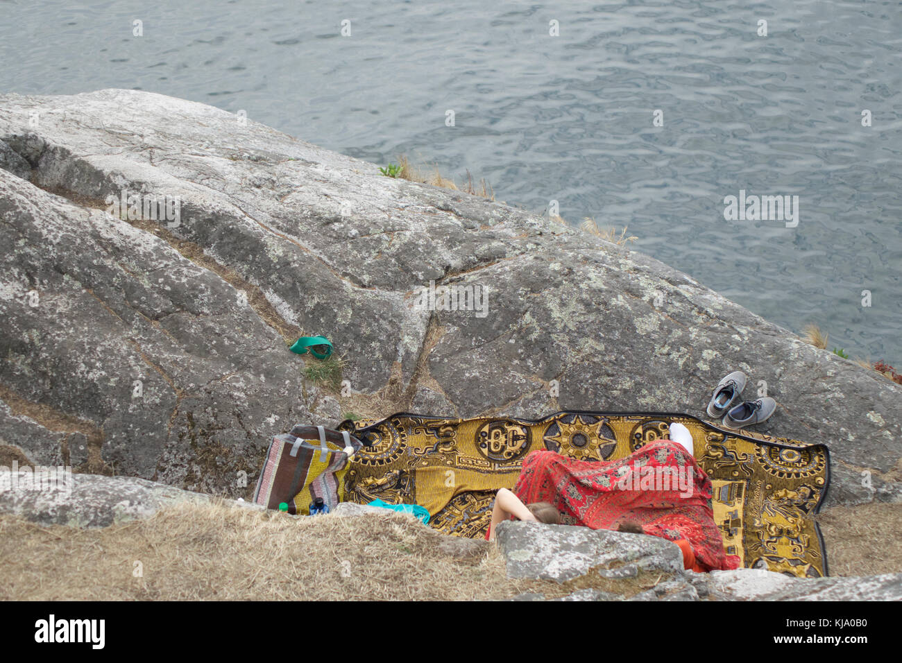 Looking down at partial view of 2 unrecognizable people seated on a colorful patterned blanket on a rock enjoying - Stock Image