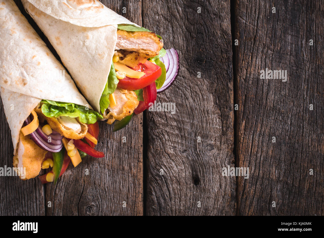 Tortilla sandwiches with fried chicken and vegetables on wooden background with blank space - Stock Image