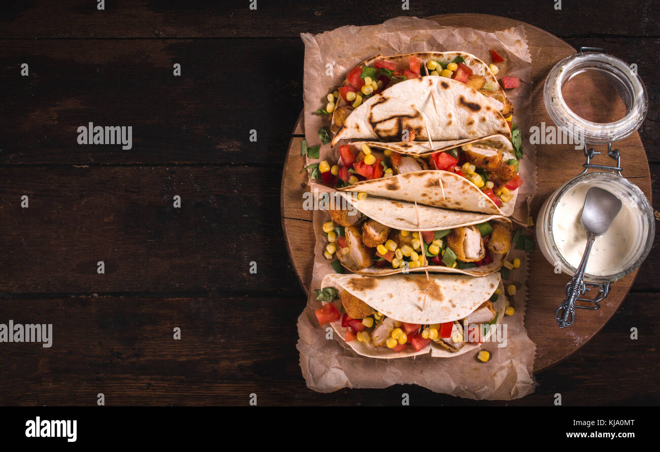 Tortilla sandwiches with fried chicken and vegetables,selective focus and blank space - Stock Image