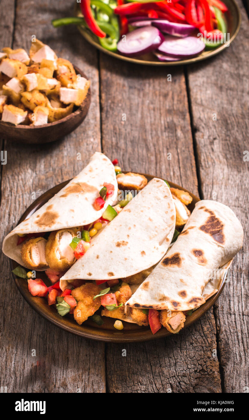 Wrap sandwiches with fried chicken meat and vegetables,selective focus - Stock Image