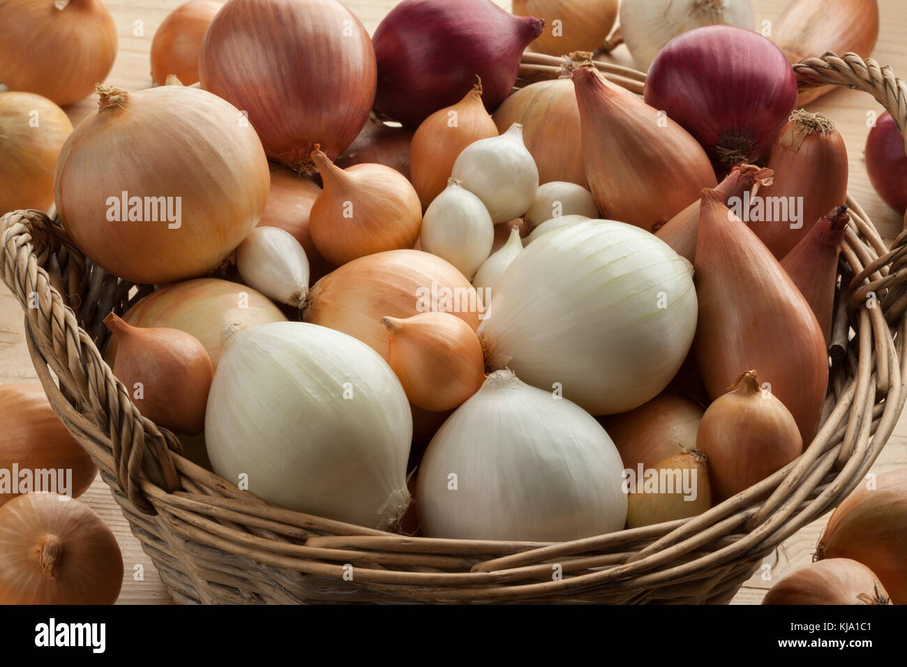 Diversity of fresh raw onions in a basket - Stock Image