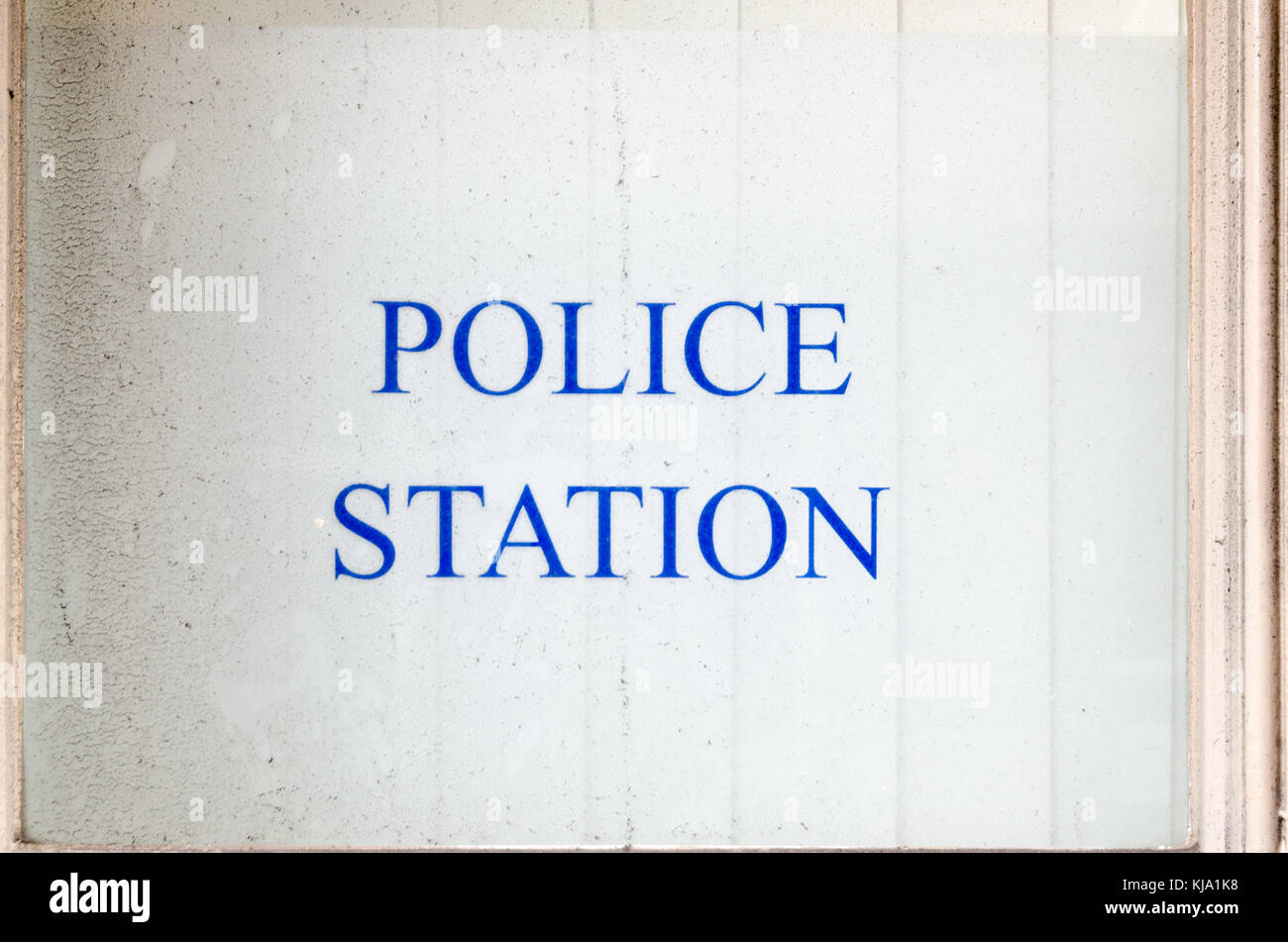 Sign for police station on glass window of police station - Stock Image