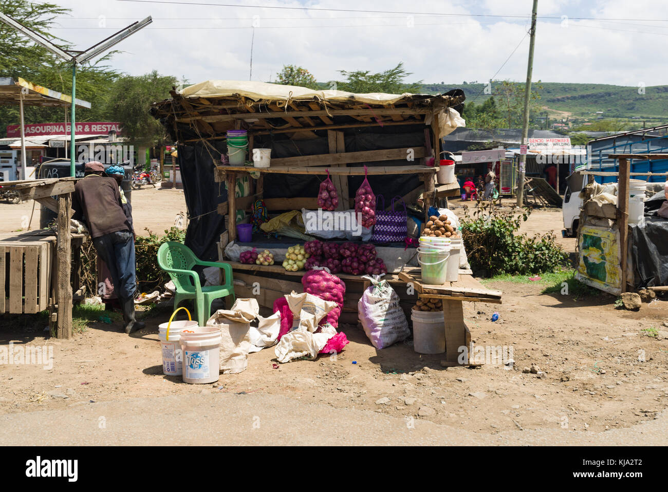 An African stands by his stall with fruit and vegetables on sale by