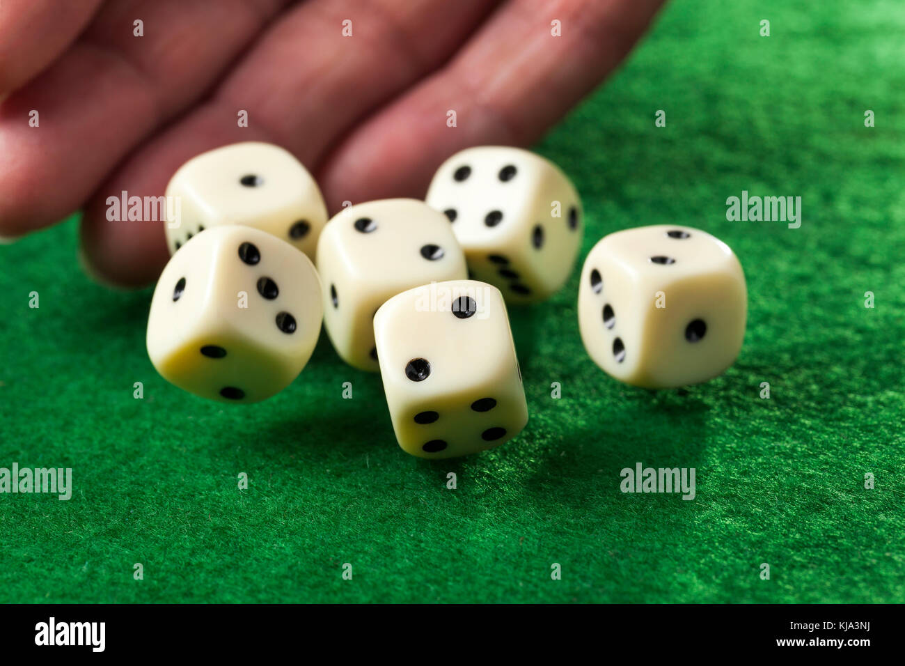Hand throwing dices on green felt Stock Photo