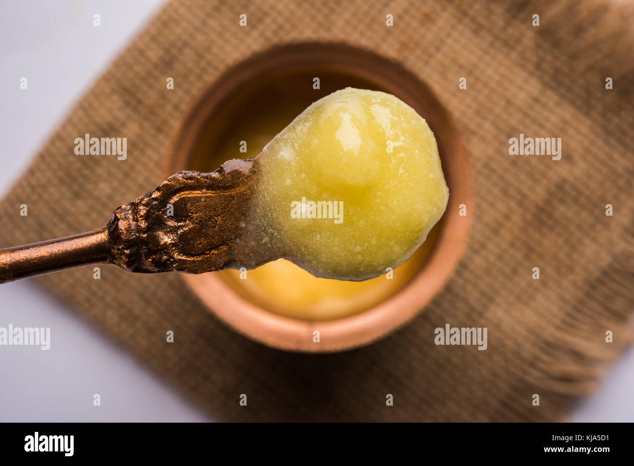 Desi Ghee or clarified butter in glass or Copper container or ceramic jar with spoon, selective focus - Stock Image