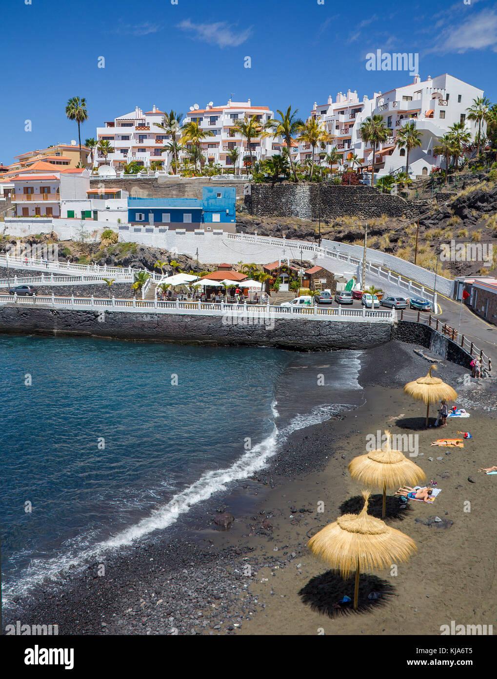 Tiny dark beach  (Piscina los chocos) at village Puerto de Santiago, Tenerife island, Canary islands, Spain - Stock Image