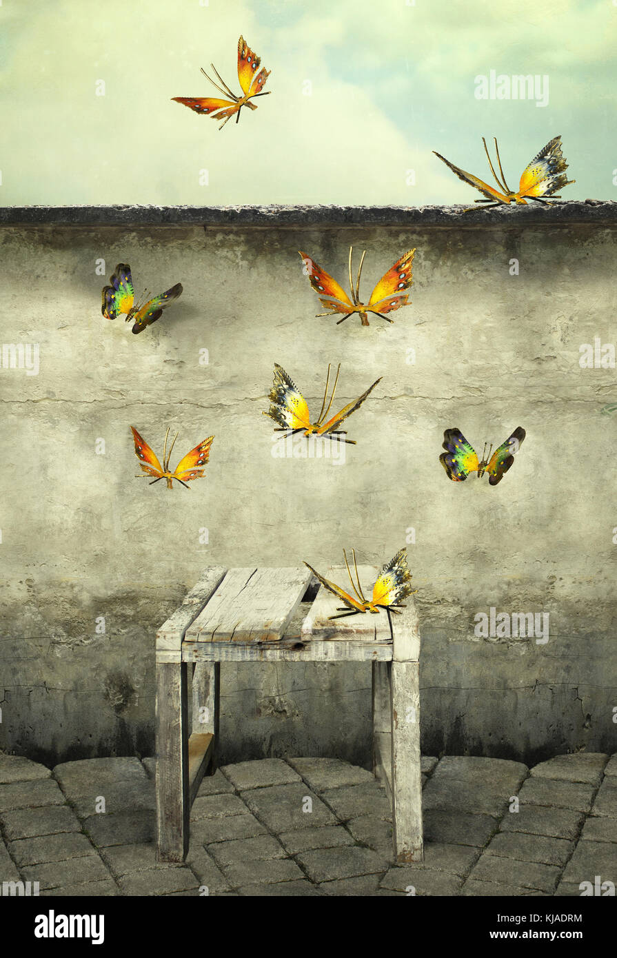 Many colorful butterflies flying into the sky with a peeling wall and a bench, illustrative photo and artistic - Stock Image