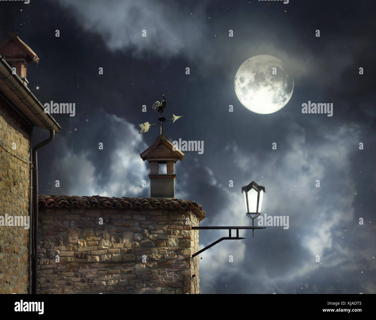 Antique roofs with weather vane rooster and chimneys in a beautiful night sky with full moon and clouds - Stock Image