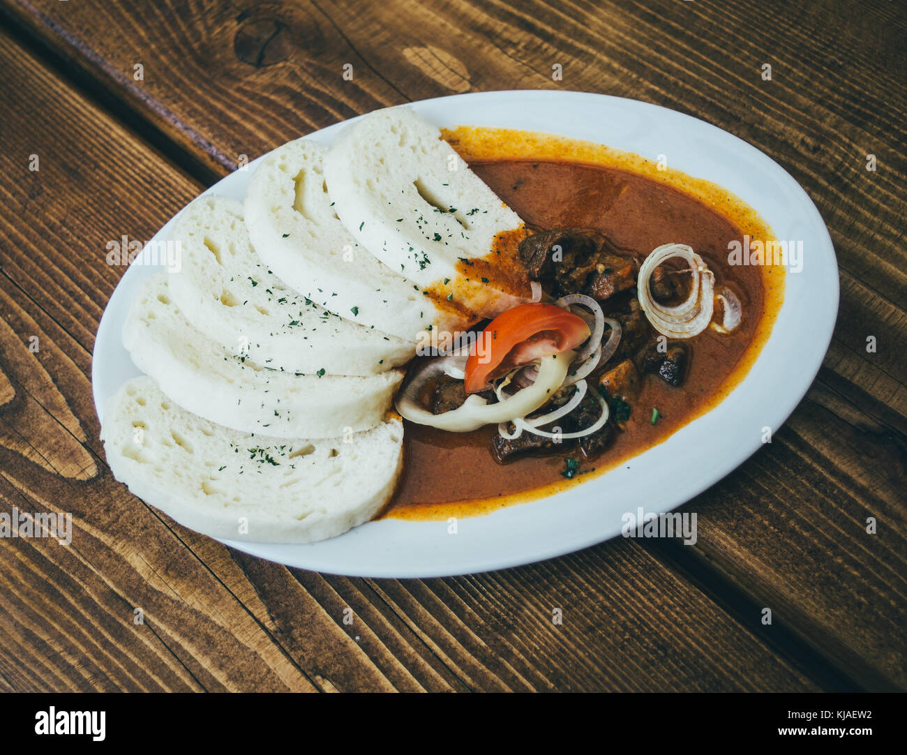 Knedliky with goulash served on a plate standing on a wooden table - Stock Image
