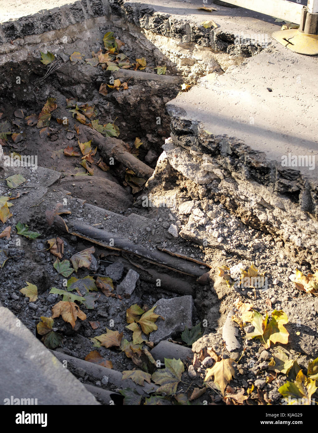 A hole in the road exposing utilities in central London England - Stock Image